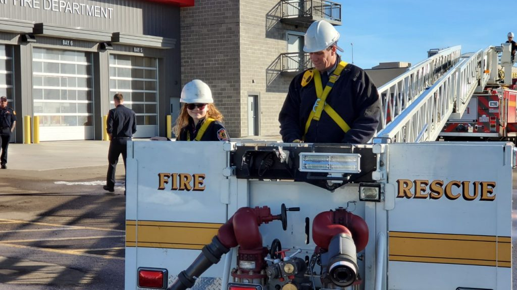 Fire Chief For A Day Mia Churn and Firefighter Kyle Reesor prepare to go up in the bucket